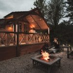 Cedar lodge by night with hot tub and fire pit